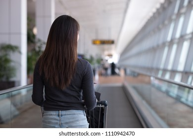 Young woman aveler walking on escalator with  luggage trolley in departure terminal in an international airport