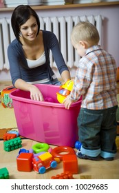 Young woman with baby boy during plaing. Woman showing toy to baby. They are at container with toys. Baby standing back to camera. Front view.