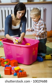 Young woman with baby boy during plaing. Woman showing toy to baby. They are at container with toys. Front view.