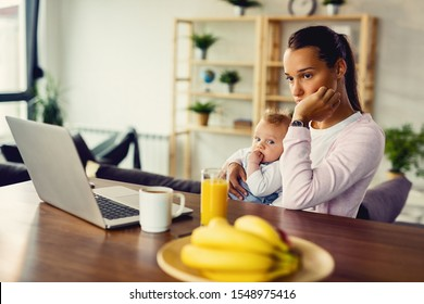 Young woman with baby experiencing postpartum depression and contemplating at home.