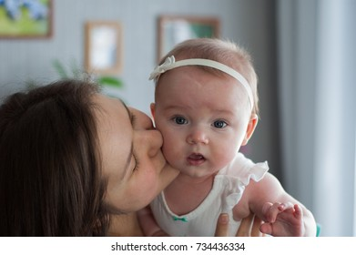 A young woman and a baby near by - the relationship of mom and daughter.