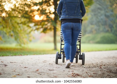 Young woman with baby stroller in the park