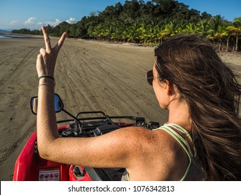 young woman from the back driving quad on the beach in costa rica