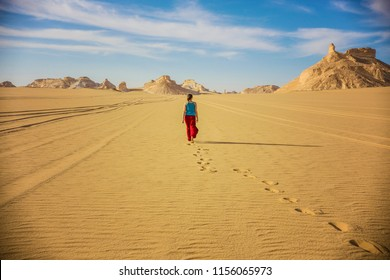 Young woman (back view) walking in the desert, Sahara desert landscape, woman in the desert, Egypt