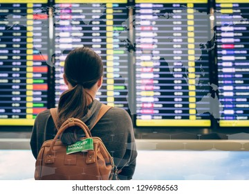 Young woman with backpack in airport watching flight timetable.