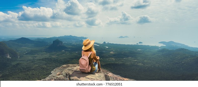 Young woman with backpack enjoying breathtaking view of the landscape from the top of mountain. Travel comcept. Back view. Banner edition.