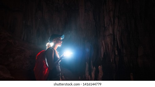 Young woman with backpack explores the cave with the torch