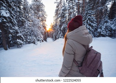 Young woman with backpack going on winter forest road in snow covered winter pine forest. Snowy weather. Big pines. Winter holidays.