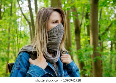 Young woman with backpack hide face with a scarf in a mixed forest Beskidy in Poland in spring time.