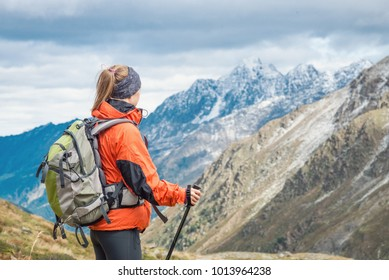 Young woman with backpack hiking in the mountains. Alps