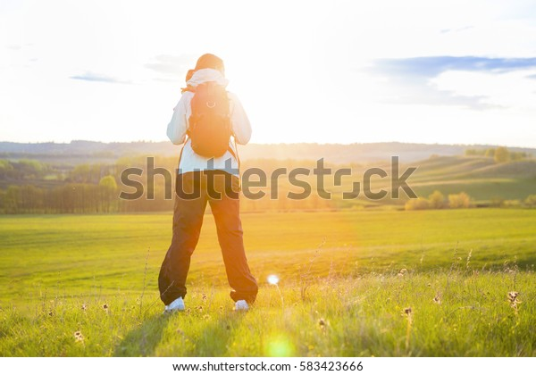 Young woman with backpack hiking in the mountains on field