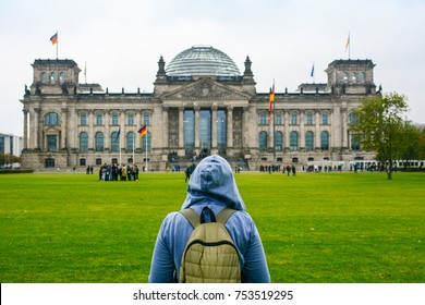 Young woman with backpack looking at Bundestag building in Berlin. Erasmus student, studying abroad and tourist concept.