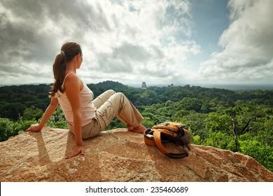 A young woman with a backpack is looking at the ruins of an ancient Maya city Tikal. National park Tikal. Guatemala