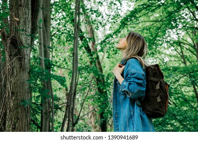 Young woman with backpack in a mixed forest Beskidy in Poland in spring time.