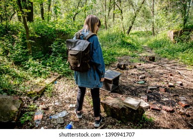 Young woman with backpack near garbage in a mixed forest Beskidy in Poland in spring time.