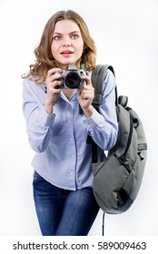Young woman with backpack and photo camera over the white background