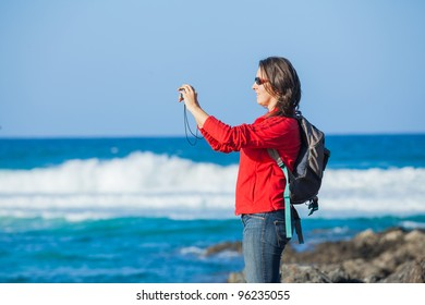 Young woman with backpack photographing a beautiful marine view
