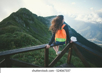 Young woman with backpack sitting high on the top of the mountain with hat and waving hair