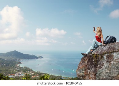 Young woman with backpack sitting on a rock and enjoying view of tropical lagoon with town