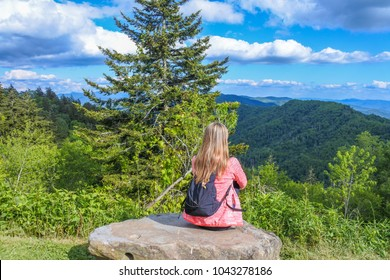 Young woman with backpack sitting on a mountain top peacefully gazing at tranquil scenic view   of the Great Smoky mountains National Park during a Summer day with blue sky.