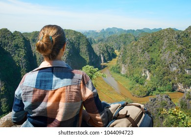 Young woman with backpack sitting on top of the mountain and enjoying river and valley view. Ninh Binh, Vietnam.Mountains landscape, travel to Asia, happiness emotion, summer hike concept.