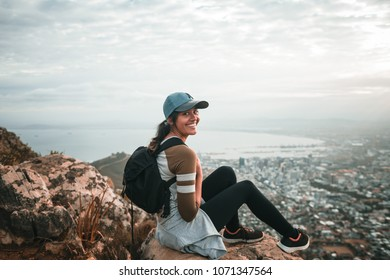 Young woman with backpack sitting on top of high mountain