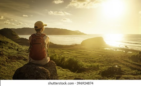 Young woman with backpack sitting on cliff and enjoying sunset over sea. Island Lombok, Indonesia.
