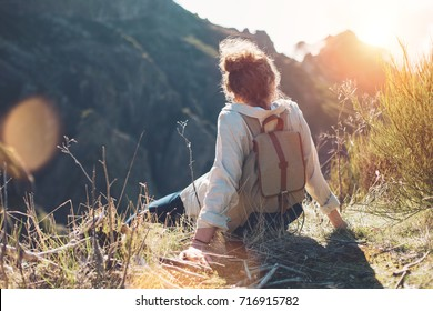 Young woman with backpack sitting on a cliff and enjoying the view of mountains, sunset and landscape.