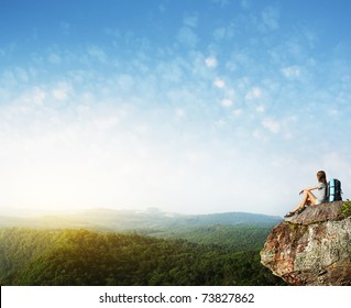 Young woman with backpack sitting on cliff's edge with raised hands and looking to a sky