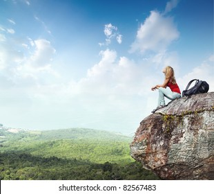 Young woman with backpack sitting on cliff's edge and looking to a sky with clouds