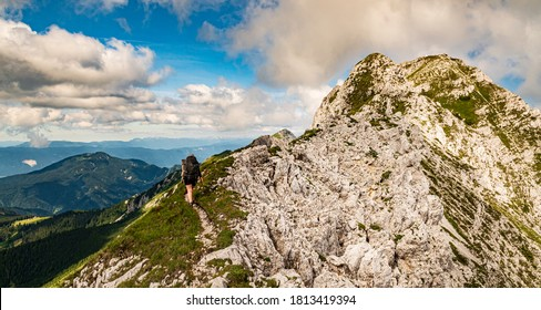 Young woman summer hiker with backpack climbing steep slopes, panoramic peaks. Female trekker in challenging terrain in Karavanke mountains, Slovenia and Karawanken mountains, Carinthia, Austria