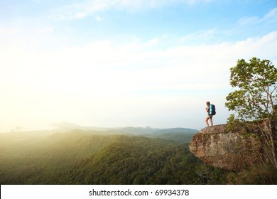Young woman with backpack standing on cliff's edge and looking to a sky