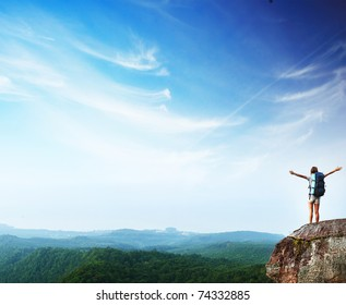 Young woman with backpack standing on cliff's edge with raised hands and looking to a sky
