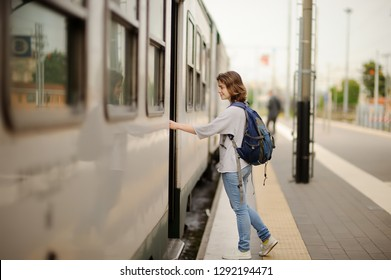 Young woman with backpack take the train. Tourism and travelling.