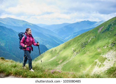 Young woman with backpack and trekking sticks hiking in the mountains of Romania. Concept healthy and active lifestyle. Girl on nature background with mighty mountains