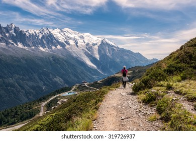 Young woman with the backpack walking on a footpath in the mountains, France.