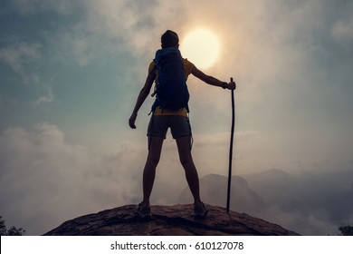 young woman backpacker enjoy the view on sunrise mountain peak