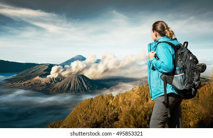 Young woman backpacker enjoying view volcano Bromo,  island Java, Indonesia. Discovering world, summer vacation concept.