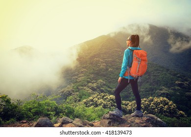 young woman backpacker hiking at forest mountain top