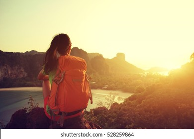 young woman backpacker hiking on seaside mountain
