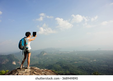 young woman backpacker on mountain peak rock use digital tablet