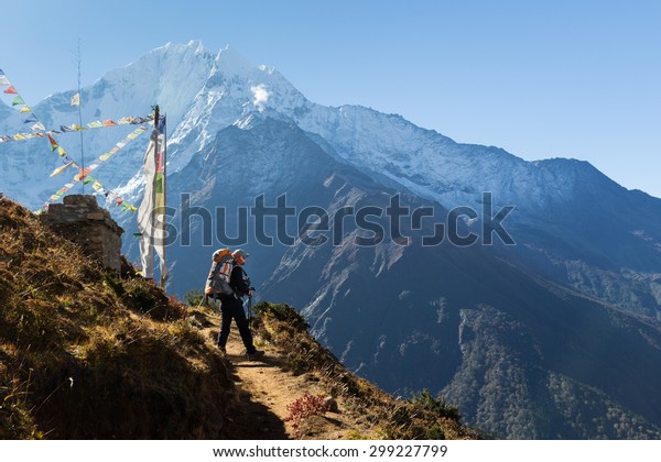Young woman backpacker standing buddhist stupa in front Kangtega mountain snow peaks ridge. Everest Base Camp route trail, Nepal trekking, Himalaya tourism.