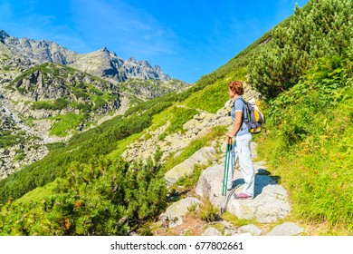 Young woman backpacker standing on hiking trail in summer landscape of High Tatra Mountains, Slovakia