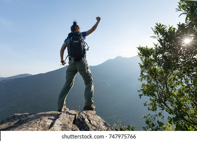 young woman backpacker standing on cliff's edge with raised hands