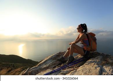 young woman backpacker at sunrise seaside mountain peak - Shutterstock ID 341026064
