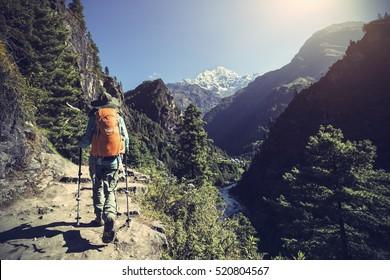 young woman backpacker trekking on himalaya mountain trail