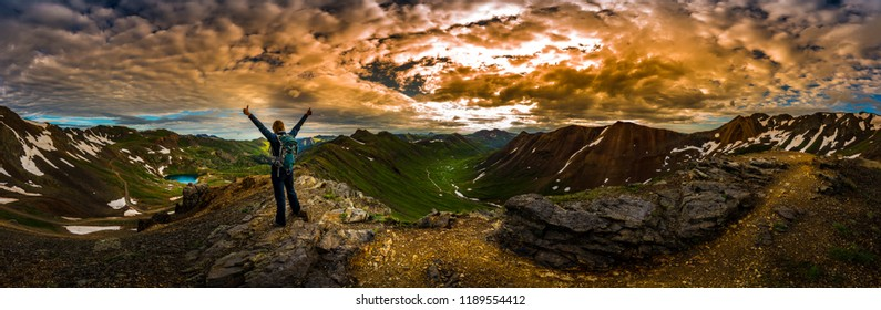 Young Woman Backpacker in Victory Pose with raised up arms on top of the Mountain Colorado USA