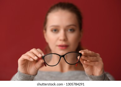 Young woman with bad sight holding eyeglasses on color background
