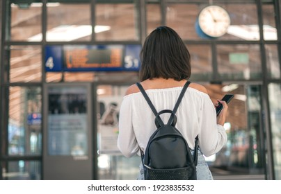 Young woman with bag and backpack in the trainstation in front of timetables. Traveling concept