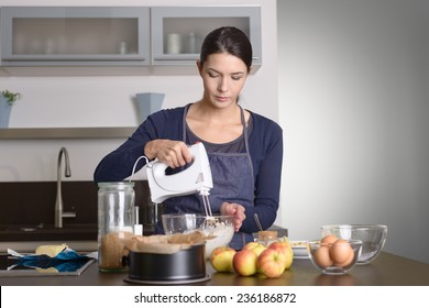 Young woman baking an apple pie in the kitchen standing at the counter in her apron using a handheld mixer to whisk the fresh ingredients in a glass mixing bowl , apples, eggs and baking tin in front